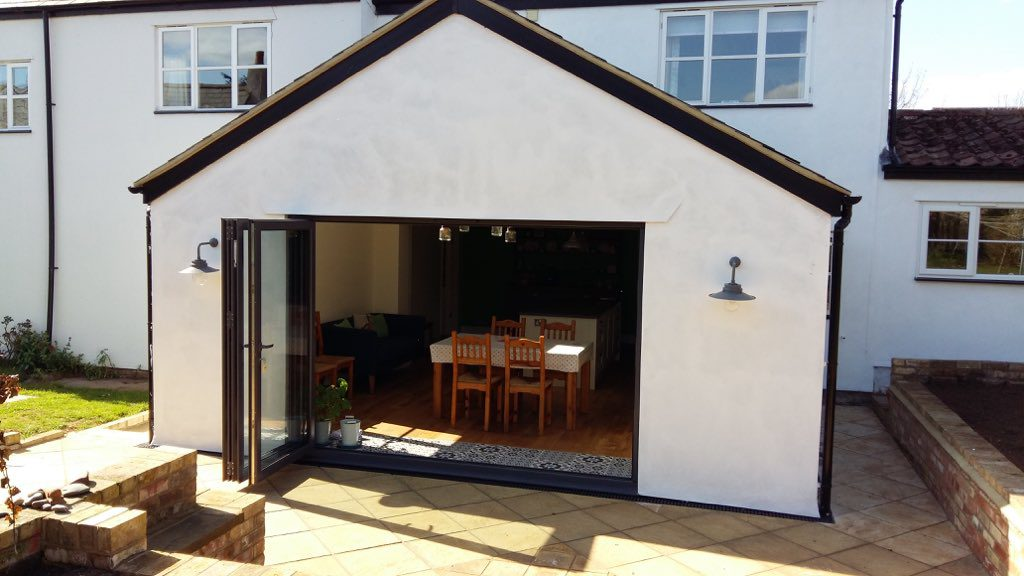 grey origin bifolding doors in a new extension rendered in a cottage