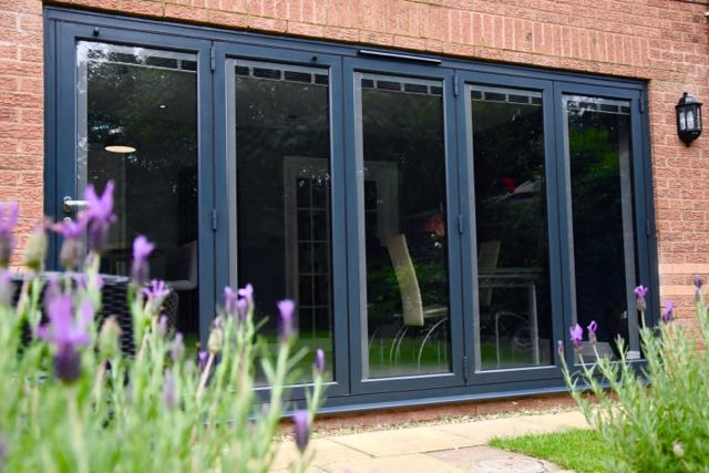 grey bifolding doors with integral glass blinds